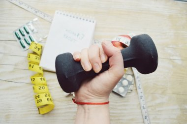 Woman hand with dumbell, pill, notes and measuring type
