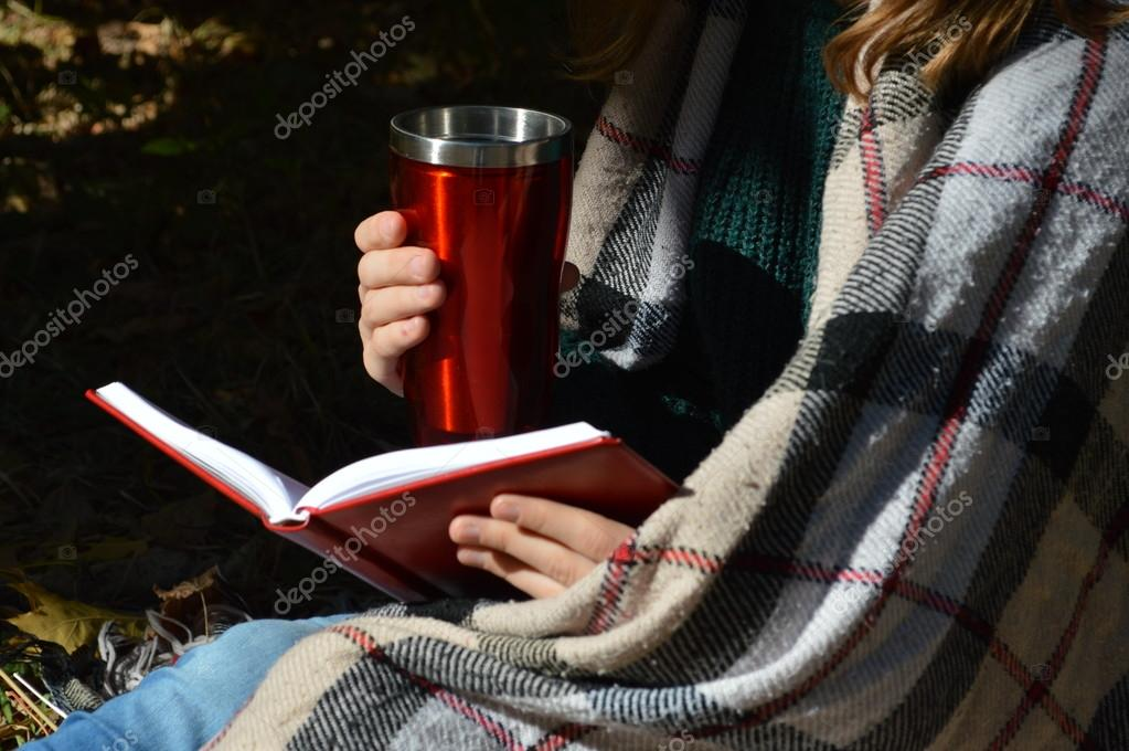 A young,beautiful girl wrapped in a warm plaid blanket drinking hot tea and reading a book in the Park