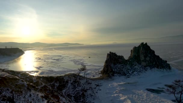 The view of the Shaman Rock, the hazy morning of sunrise at Burkhan cape. North line of Olehun Island, Lake Baikal, ice field icicle view. Russia. Jan. 2019