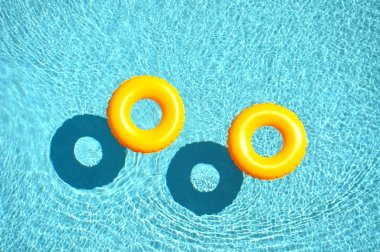 Two yellow pool floats