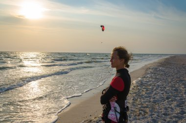 A young woman is looking at sunset the Black sea and  kitesurfing