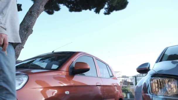 handsome young man gets in an orange sport car parked by opening the car door near the road under blue sky 4K high resolution