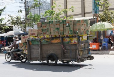 Workers transport goods by motorbike and cart in the Thai-Cambodian border town