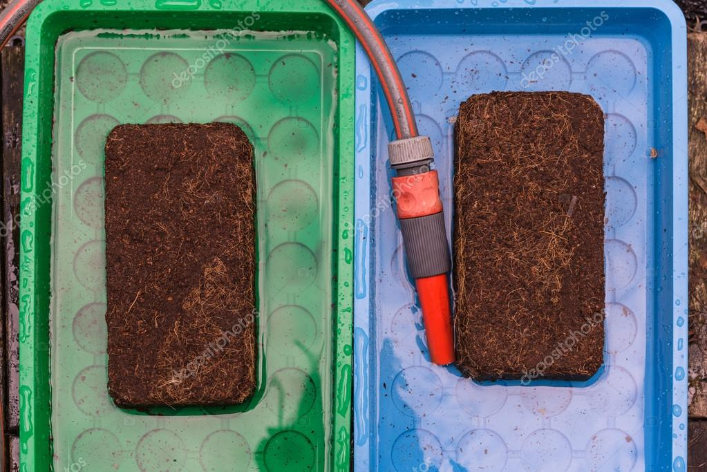 Aerial view wet peat full blocks in tablet with garden hose