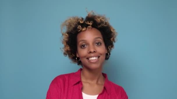 Fiatal afrikai nő göndör haj mosolygós álló színes fal.