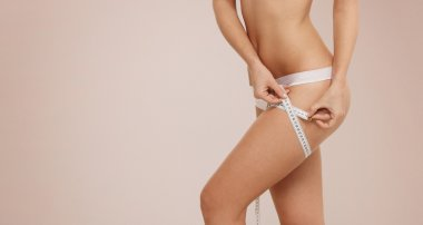 Time for diet slimming weight loss. Fitness woman fit girl in lingerie with measure tape measuring her thigh.