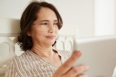 Smiling mature woman in glasses using digital tablet pc lying on her bed in a bedroom.