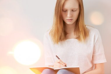 Close up lifestyle image of pretty young teenage girl sitting on her floor and making notes to her diary. Bright colors.