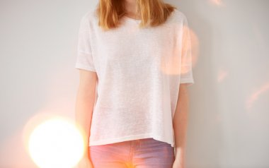Young girl wearing blank t-shirt and blue jeans. Wall background, flare light