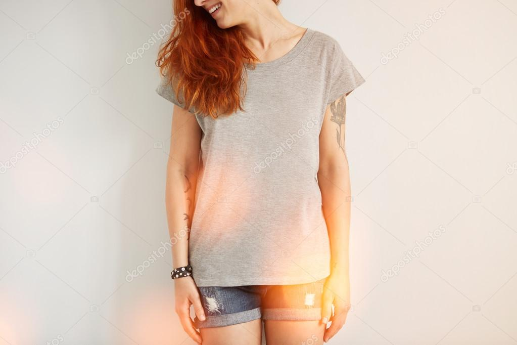 Young girl wearing grey blank t-shirt and blue jeans shorts. Concrete white wall background, flare light