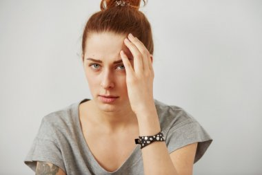Closeup portrait young upset sad woman thinking deeply about something with headache holding her hands on head looking stressed isolated on gray wall background. Negative human facial expression