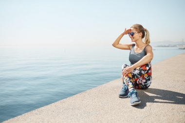 Fitness healthy blonde woman runner relaxing after city running and workout outdoors. Young Caucasian fit girl looking and enjoying view of deep sea.