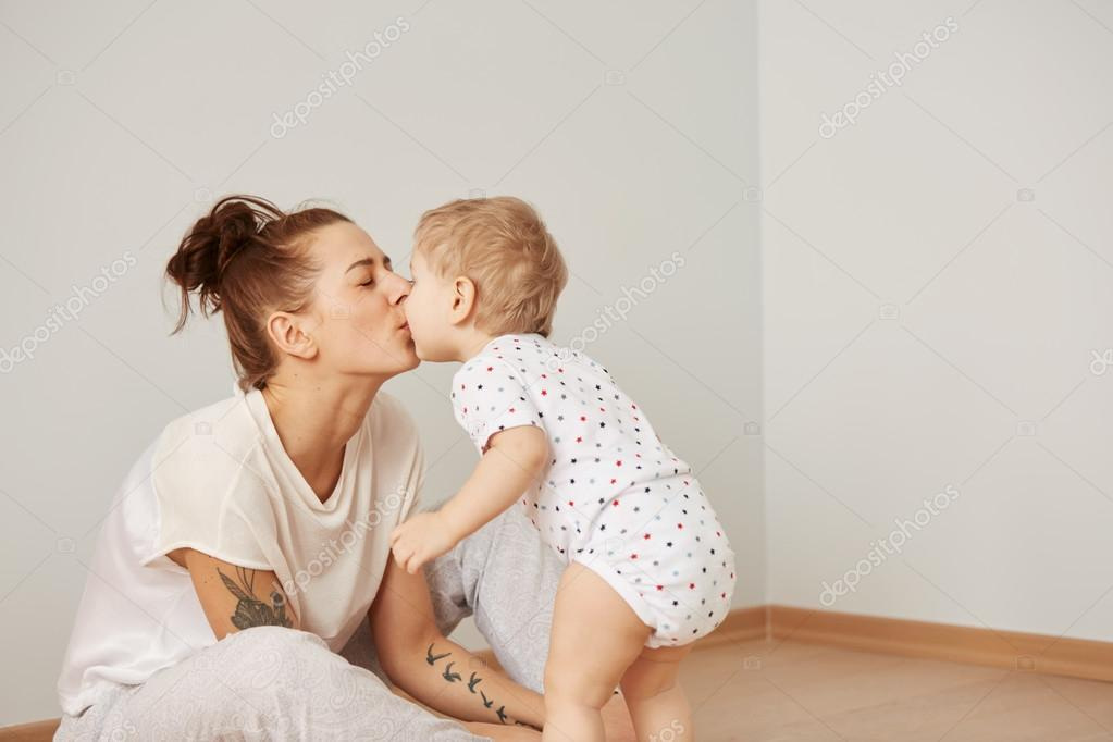 Mother and child on a white bed. Mom and baby boy in diaper playing in sunny bedroom. Parent and little kid relaxing at home. Family having fun together at the weekend together. Selective focus