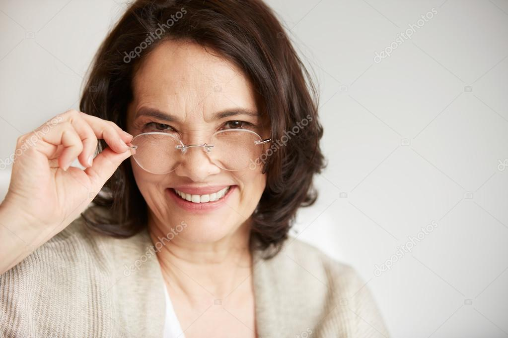 Attractive middle-aged brunette woman with a beautiful smile sitting against apartments background looking directly at the camera. Close up portrait of a senior middle aged lady relaxing at home.