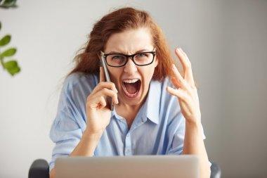 Portrait of a young irritated businesswoman wearing glasses and shirt looking with anger at the camera. Headshot of an outraged female boss shouting on the cell phone while working on her laptop in th