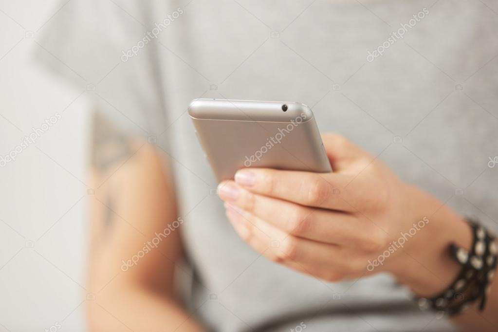 Cropped shot view of female hands holding cell phone, young woman texting on mobile telephone during work break on the gray background