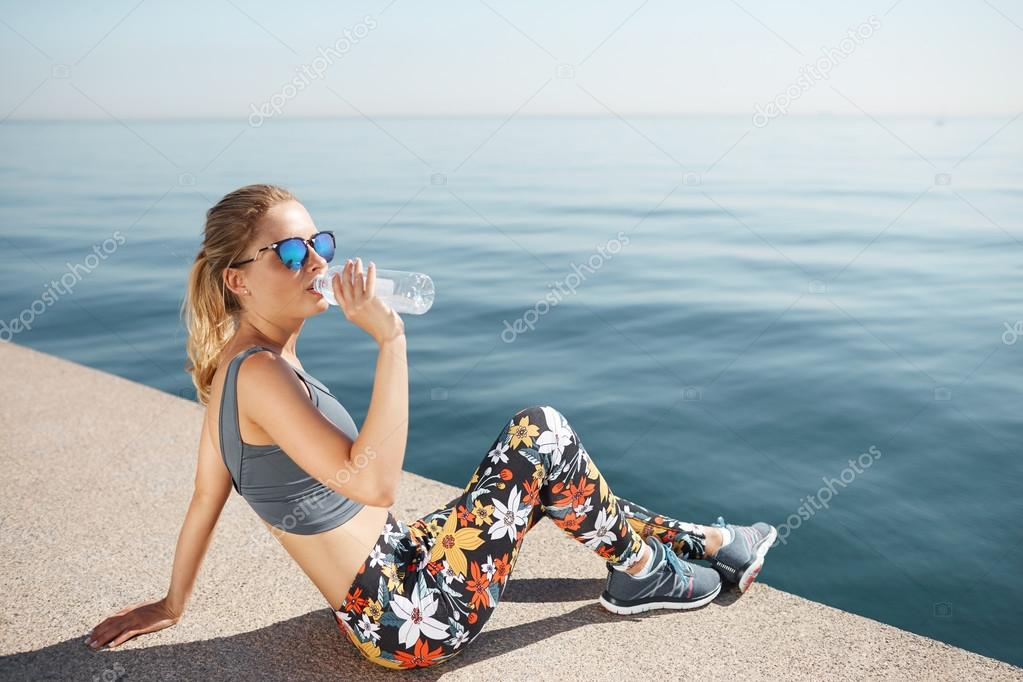 Portrait of a fit young woman resting after successful jogging workout outdoors. Pretty athlete blond wearing sportswear and sunglasses drinking water while sitting on the beach during physical traini