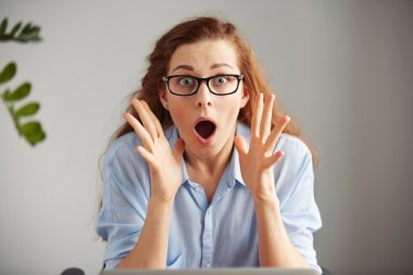 female office worker sitting with surprised expression