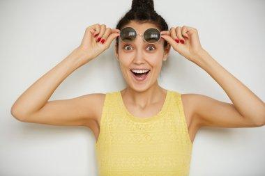 woman wearing holding round sunglasses