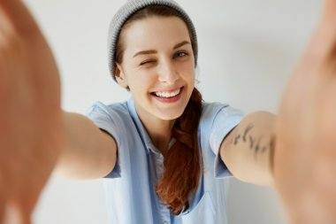 Wide-angle view of happy beautiful hipster girl in trendy clothes having fun while posing against white isolated wall. Student girl looking, smiling and winking at the camera lens. Body language