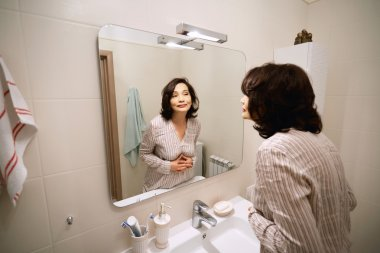 Portrait of beautiful adult woman of middle age looking at herself in the mirror and smiling. Elderly female applying anti-aging cream or make-up in the bathroom before going shopping in the morning