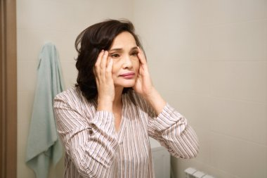 Portrait of middle-aged woman's reflection. Beautiful brunette elderly female wearing pajamas, applying anti-aging cream, looking for ageing signs, standing in front of the mirror in the bathroom.