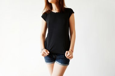 Cropped shot of young Caucasian brunette model in blank black T-shirt and jeans shorts. Female office worker wearing casual clothes at home after hard working day in the office. Lifestyle concept