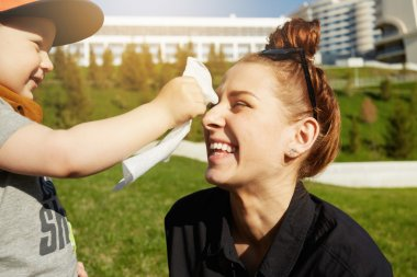 Close up shot of hipster teenage girl spending time with her little nephew on summer morning in the city park. Beautiful young mother with her adorable son in stylish clothes having fun together