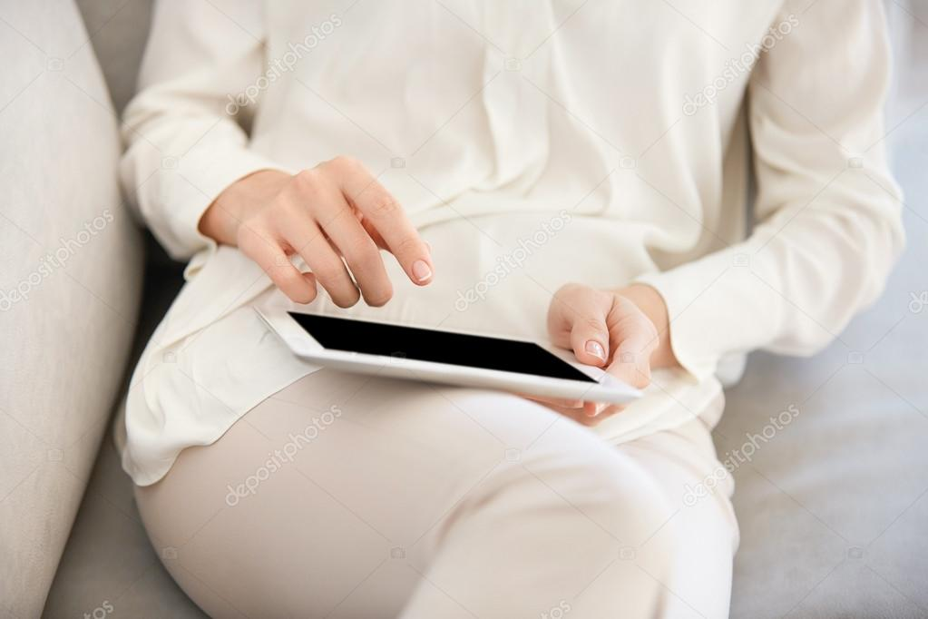Cropped image of attractive young woman wearing trendy clothes using digital tablet for online dating. Female office worker communicating with friends via social networks after hard day in the office
