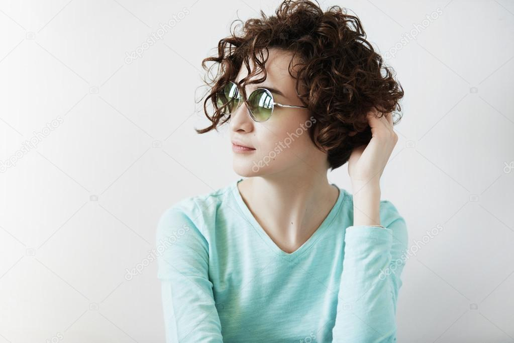 Close up isolated view of beautiful young brunette woman with perfect healthy skin wearing stylish shades and casual top, looking away with thoughtful expression on her face, touching her curly hair