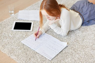 woman lying on floor making notes