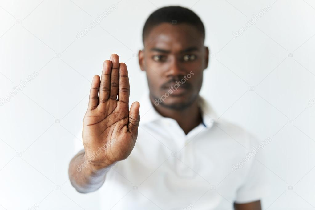 serious African male holding hand in stop sign