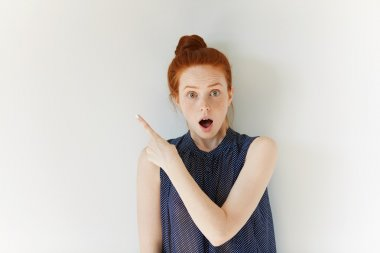 Surprised young redhead woman