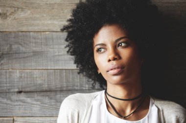 Highly-detailed portrait of beautiful dark-skinned young student girl with healthy skin and Afro hairstyle, wearing stylish clothes, looking away with dreamy expression, making plans for future
