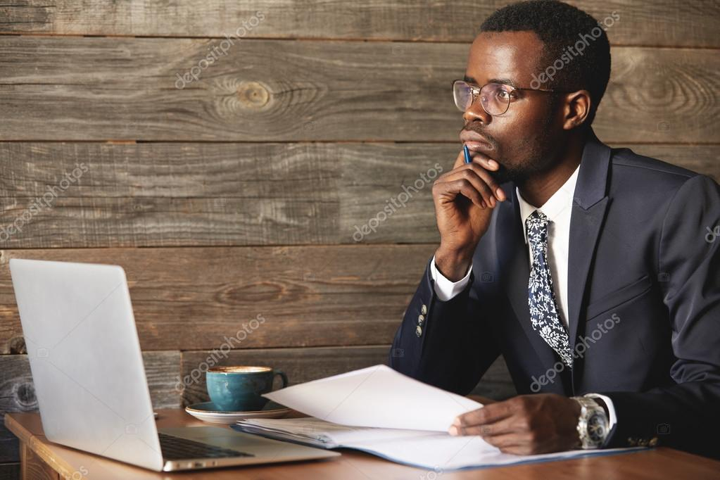 Handsome Young African Man Wearing Formal Suit Sitting At