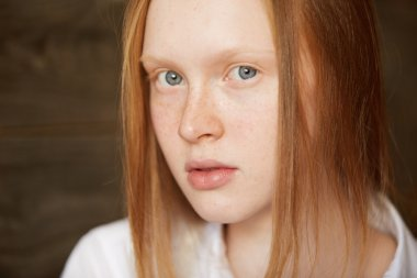 Youth and skin care concept. Highly-detailed portrait of beautiful Caucasian teenage girl with ginger hair and perfect clean skin with freckles, posing against wooden wall background in white shirt