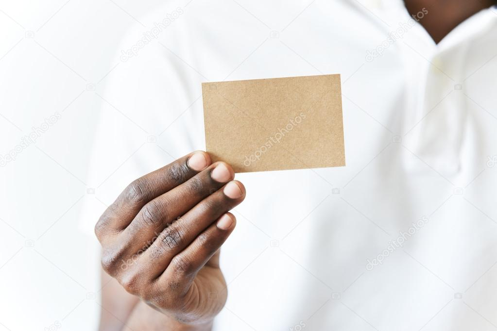 Close up of African man\'s hands holding business card with copy ...