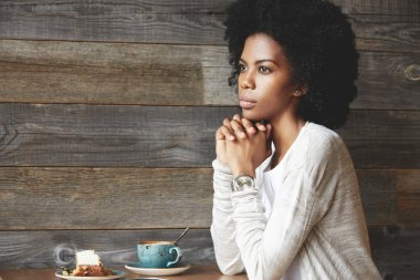 Young attractive dark skinned female at a cafe table, drinking coffee with cake, sitting in thinking pose, resting chin on her clasped hands, looking away with a reflective expression on her face