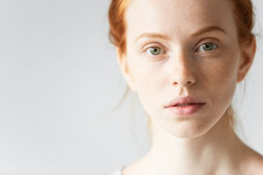 Skin care and beauty concept. Highly-detailed portrait of the face of pretty redhead female with pure healthy ideal skin with freckles looking at the camera with a faint smile and with parted lips