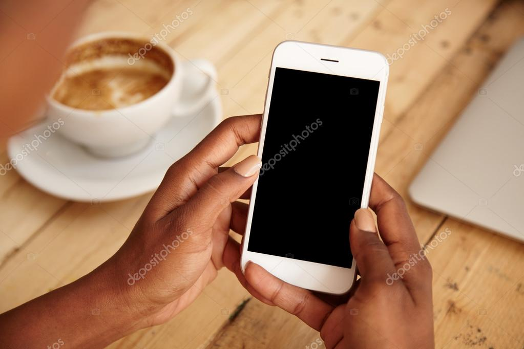 Cropped shot of black female's hands holding mobile phone with blank copy space screen for your text message or promotional content. Young woman watching videos using cell phone sitting at cafeteria