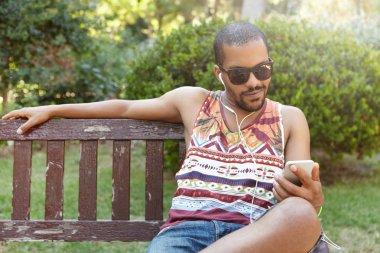 African guy in earphones sitting on bench