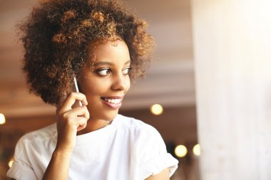 People, technology and communication. Happy dark-skinned girl with Afro haircut talking on smart phone with her boyfriend, standing against cafe interior background with copy space for your content