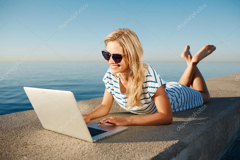 Cheerful girl lying at summer on the beach near sea and talks to