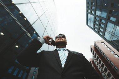 Bottom view portrait of successful business man talking on smart