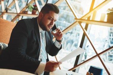 Portrait of successful business man talking on smart phone insid