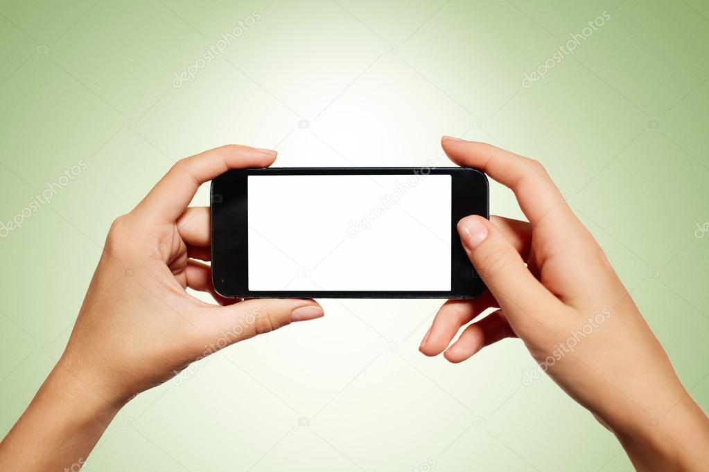 Hand holding smartphone with blank screen isolated on green back