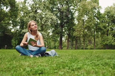 Happy young blonde woman with digital tablet sitting at park.