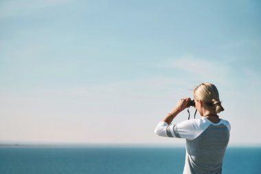 Woman tourist looking through binoculars at distant sea, enjoyin