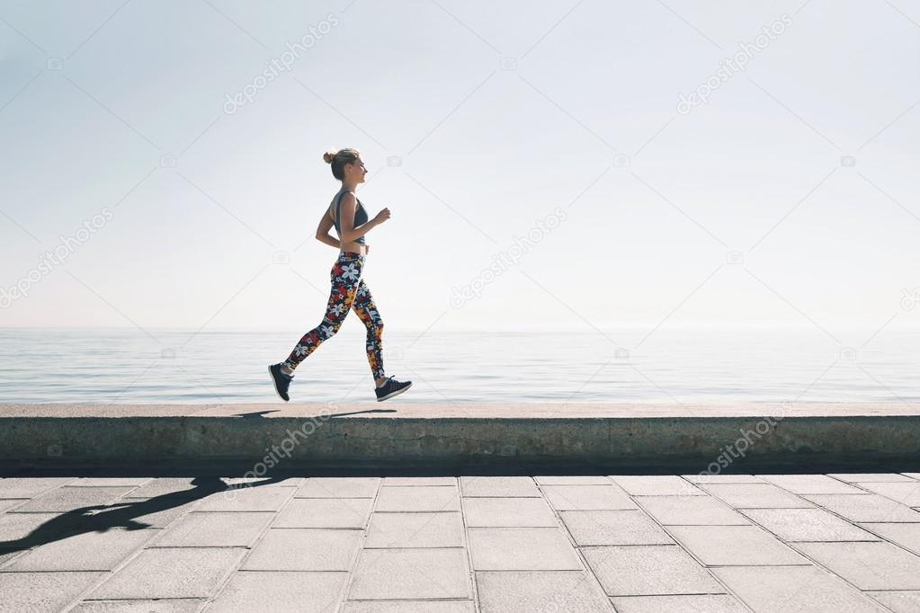 jogging athlete young woman running at sea background