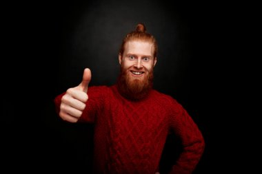 Smiling bearded man showing thumb-ups. Happy man in red knitted sweater satisfying his lifestyle on black background.